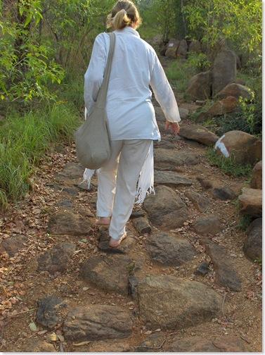 Carol walks barefoot up the path