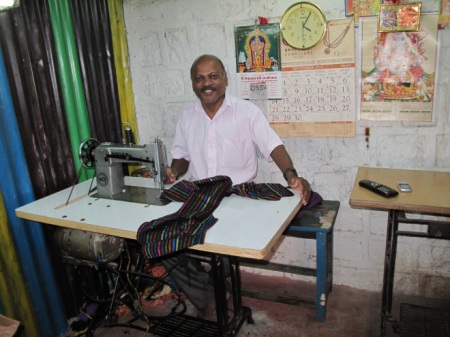 This excellent tailor cheerfully works in a cramped, hot, leaky tiny tin shed.